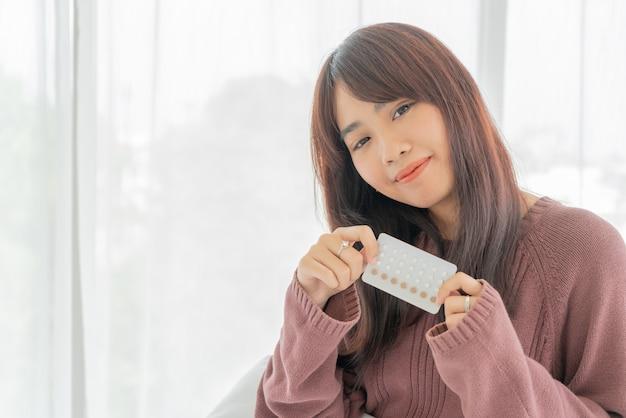 Азиатская женщина, держащая противозачаточные таблетки