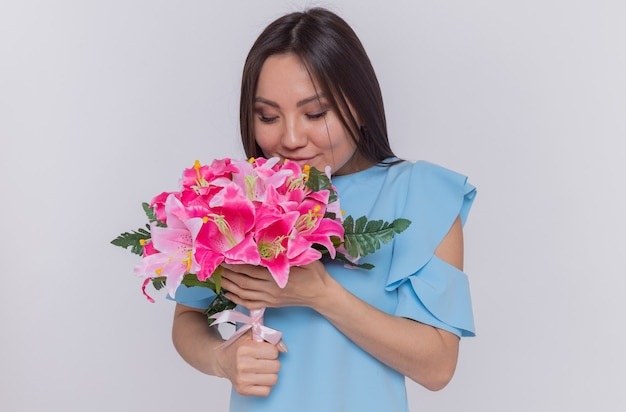 白い壁の上に立って国際女性の日を祝って幸せで陽気な花の花束を保持しているアジアの女性