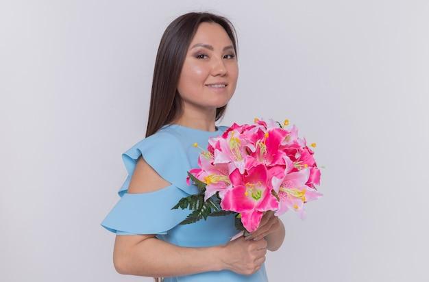 白い壁の上に立って国際女性の日を祝って幸せで陽気な笑顔に見える花の花束を保持しているアジアの女性