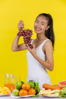 An asian woman holding a bunch of grapes, and on the table there are many fruits.