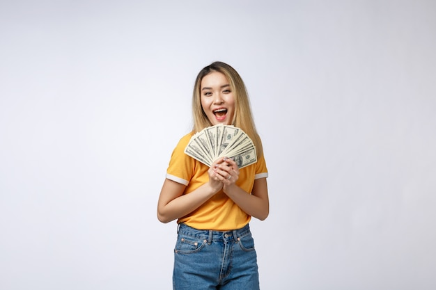 Asian woman holding cash notes isolated in white background