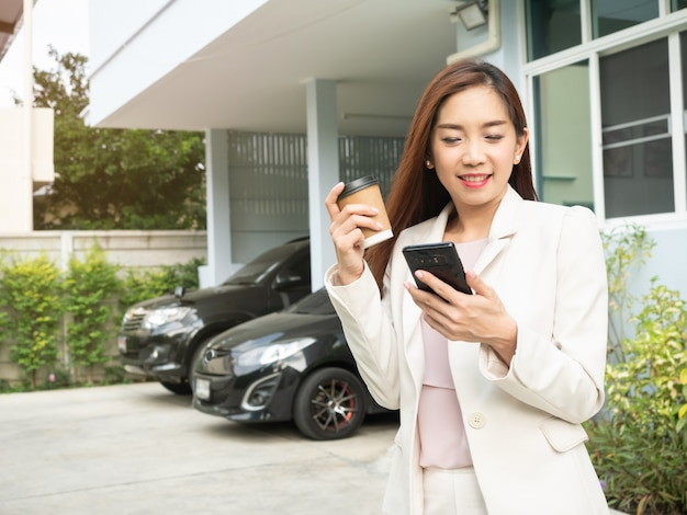 Asian woman holding coffee cup and using smartphone while standing in front of house.