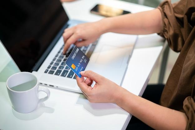 クレジットカードを保持し、自宅からオンラインショッピングを注文するアジアの女性。 eコマース、オンラインショッピング、またはオンライン決済の概念