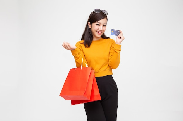 Азиатская женщина, держащая кредитную карту и красные хозяйственные сумки, изолированные на белой стене