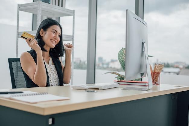 Азиатская женщина, держащая кредитную карту и использующая настольный компьютер с онлайн-покупками и работающей из домашней концепции.