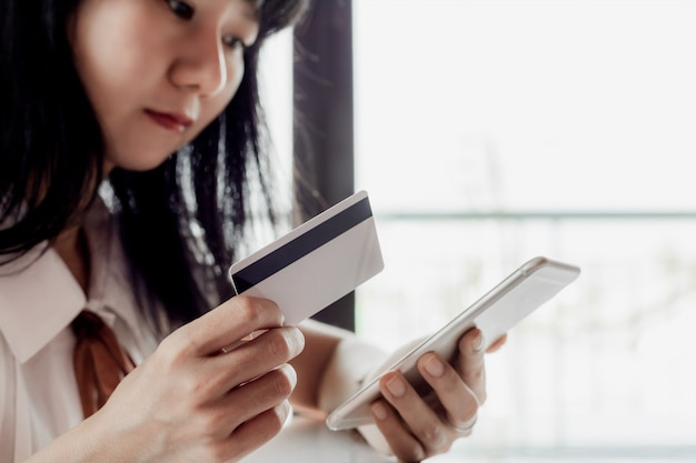 Asian woman holding a credit card and using smartphone