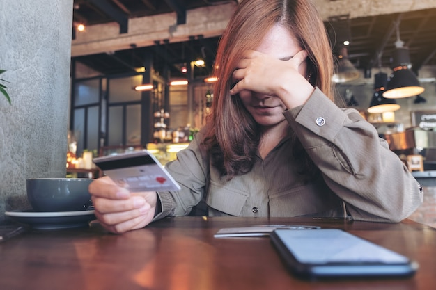 Asian woman holding credit card with feeling stressed and broke, mobile phone on the table