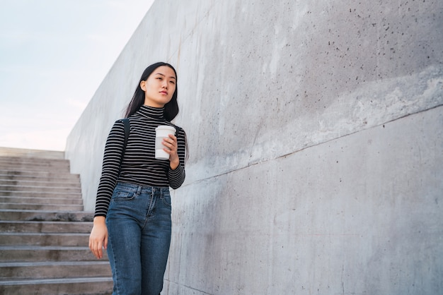 Asian woman holding a cup of coffee.