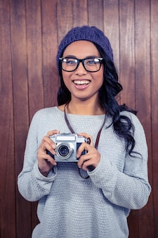 Asian woman holding digital camera against wooden wall