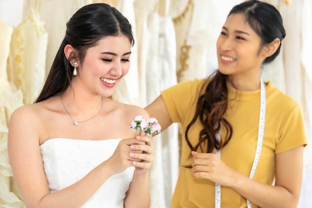 テーラーでお店でウェディングドレスの測定花を保持しているアジアの女性。