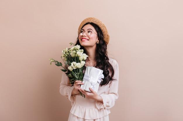 花とプレゼントを持っているアジアの女性。ベージュで分離されたトルコギキョウの花束を持つインスピレーションを得た日本人女性のスタジオショット。