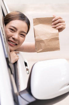 Азиатская женщина, держащая мешок еды от привода через ресторан