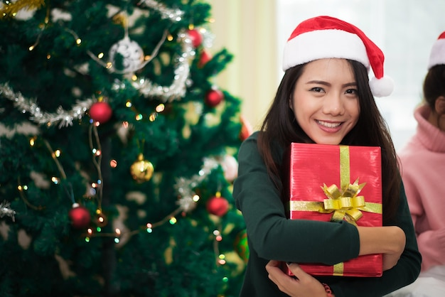 Asian woman holding a gift or present with christmas tree and decor
