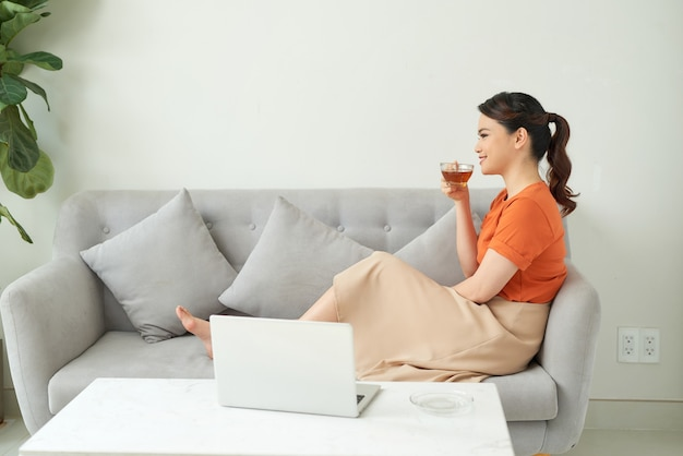 Asian woman holding glass of tea and working on laptop.