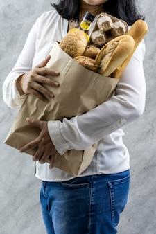 食料品の紙の袋を保持しているアジアの女性