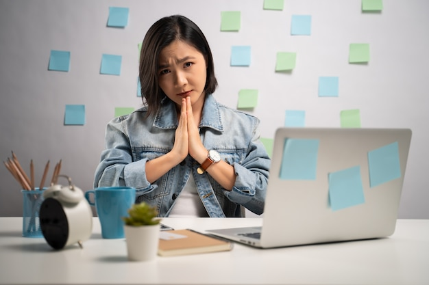 Asian woman holding hands in prayer and working on a laptop at home office. . work from home. prevention coronavirus covid-19 concept.