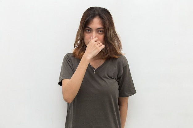 Asian woman holding her nose because of a bad smell