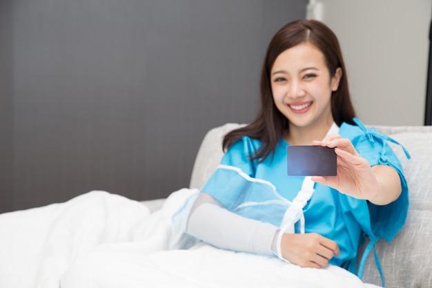 보험 카드를 들고 팔에 환자 양복을 입고 아시아 여자