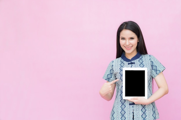 Asian woman holding ipad isolated on pink background