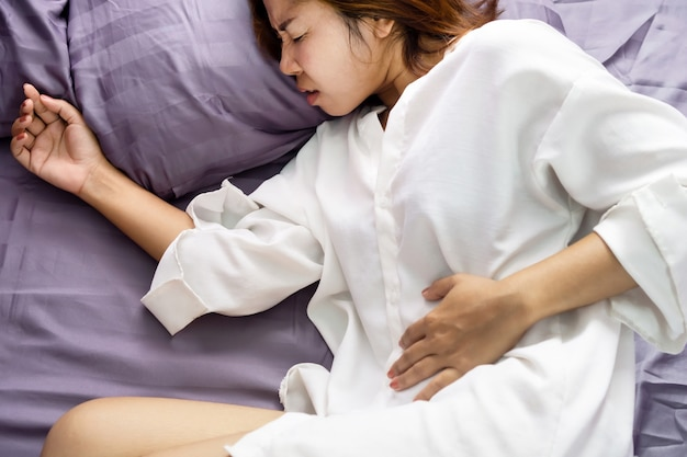 Asian woman holding left side of stomach pain in bed