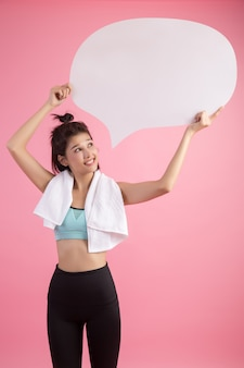Asian woman holding and looking up to speech bubble with empty space for text on pink