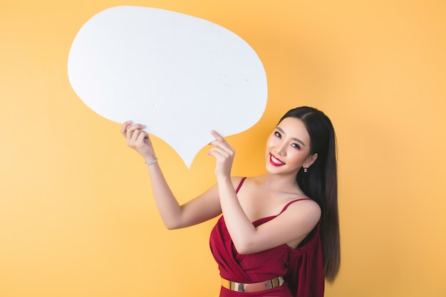 Asian woman holding and looking up to speech bubble with empty space for text