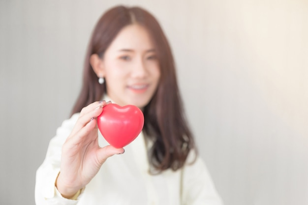Asian woman holding love heart shape. health care concept.