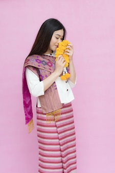 Asian woman holding marigold garland isolated on pink background