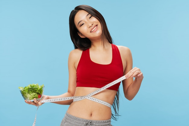 Asian woman holding measuring tape and salad bowl