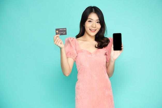Азиатская женщина, держащая мобильный телефон и кредитную карту, изолированные на зеленом.