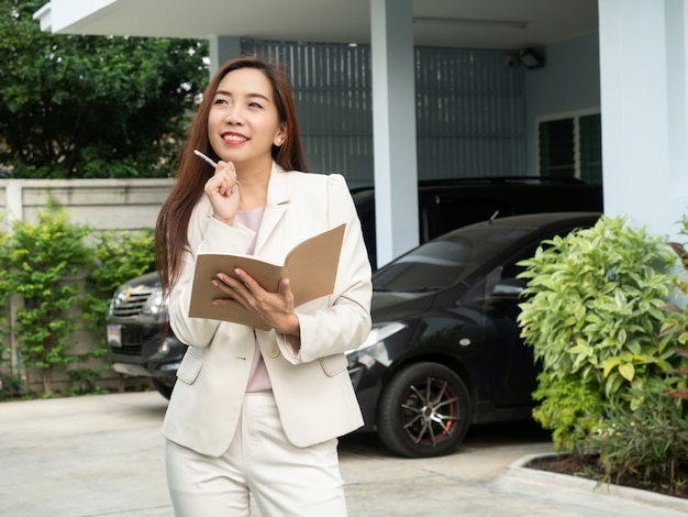Asian woman holding notebook while standing in front of house.