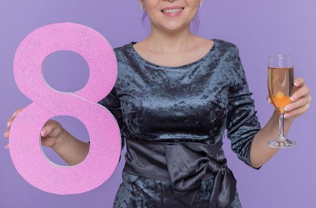 紫色の壁の上に立って国際女性の日を祝う段ボールとシャンパンのガラスで作られた8番を保持しているアジアの女性