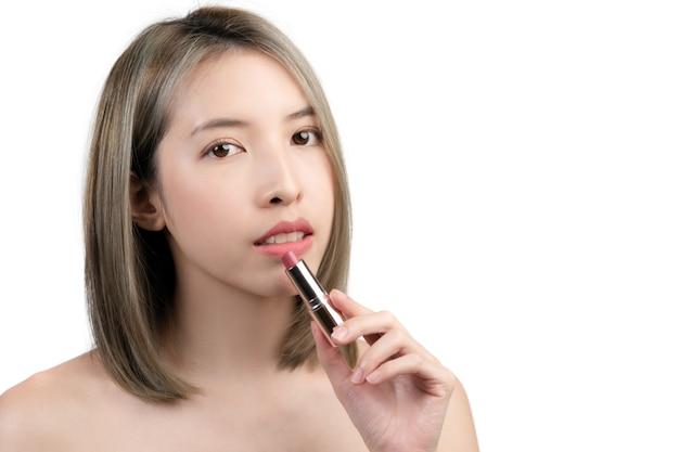 白い背景で隔離の口紅を保持または提示するアジアの女性。