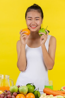 Asian woman holding oranges on both sides, and on the table there are many fruits.