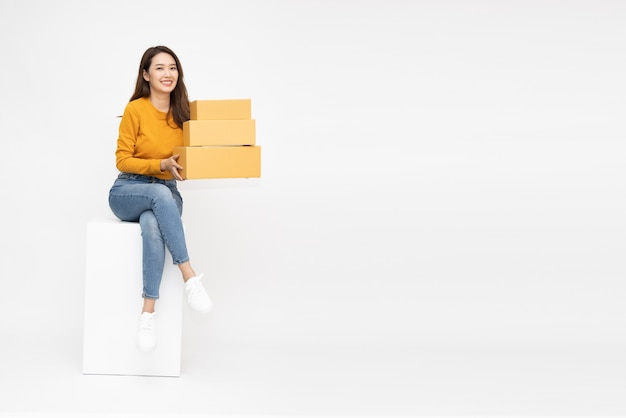 Asian woman holding package parcel box and sitting on white box isolated on white background