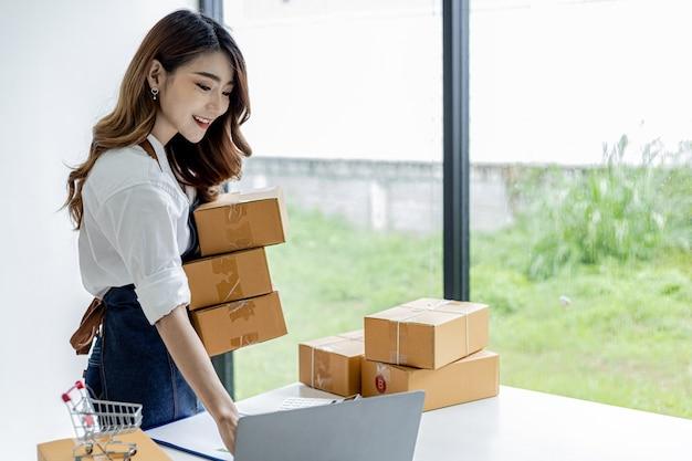 소포 상자를 들고 노트북으로 주문을 확인하는 아시아 여성, 그녀는 온라인 상점을 소유하고 개인 운송 회사를 통해 포장하고 배송합니다. 온라인 판매 및 온라인 쇼핑 개념입니다.
