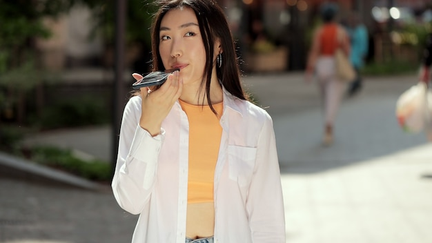 Asian woman holding phone speak activate virtual digital voice assistant on smartphone girl using smart phone voice recognition dictates thoughts voice dialing message