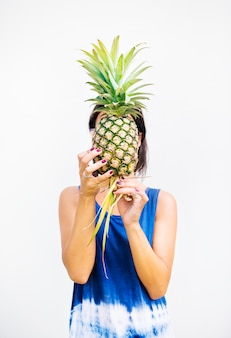 Asian woman holding pineapple covering face