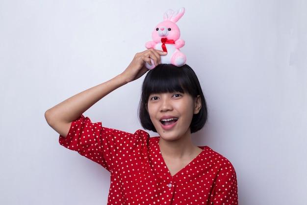 愛とバレンタインの概念でピンクのバニー人形を保持しているアジアの女性