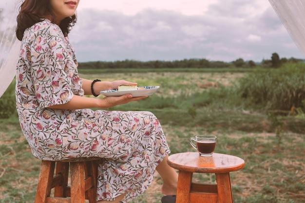 チーズケーキと屋外のコーヒーカップのプレートを保持しているアジアの女性。