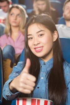 Азиатская женщина, держащая попкорн ведро, показывает палец вверх, весело улыбаясь в кино