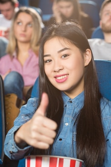 Asian woman holding popcorn bucket showing thumbs up smiling cheerfully at the cinema