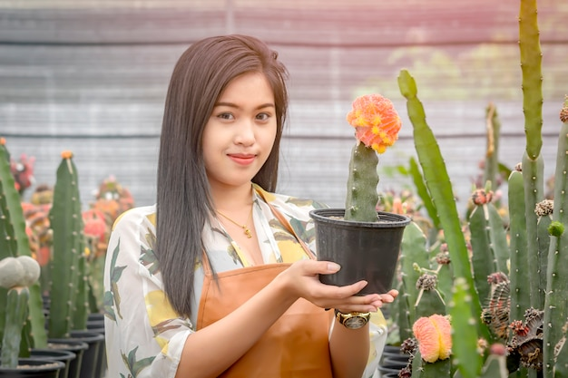 Asian woman holding a pot of colorful cactus that has just been extended to breed
