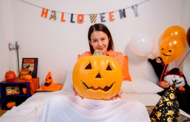 Азиатская женщина, держащая лицо тыквы для фестиваля хэллоуина дома. украшение спальни для детского и семейного праздника осенью и осенью.