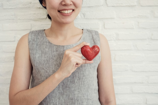 Asian woman holding red heart, health insurance, donation charity concept