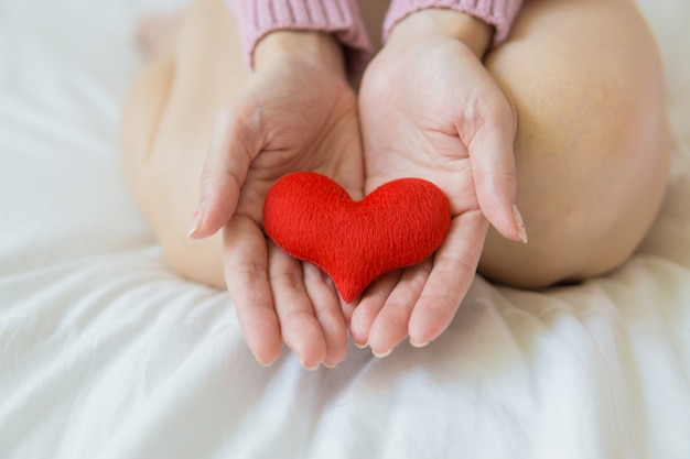 Asian woman holding a red heart in her hands.