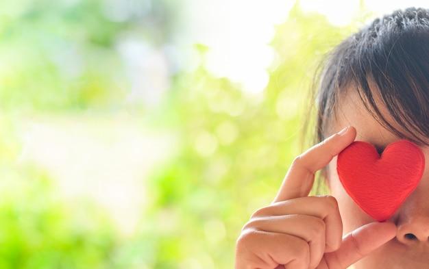 目を閉じて赤いハートを保持しているアジアの女性