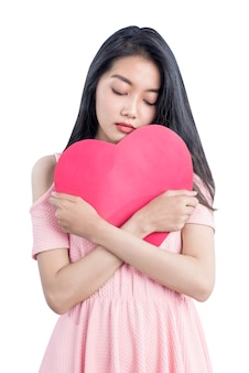 Asian woman holding a red hearts with sad expression isolated over white background
