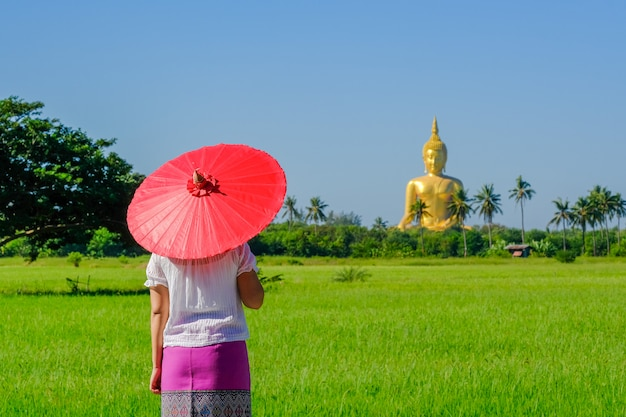 An asian woman holding a red umbrella walking on a wooden bridge in the rice field with a large golden buddha image.