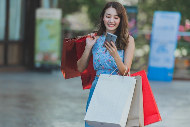 손에 쇼핑백과 스마트 폰을 들고 아시아 여자